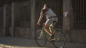 Το αγόρι οδηγά το ποδήλατο στο πεζοδρόμιο απόθεμα βίντεο