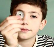 Το αγόρι ο νομισματικός συλλέκτης παρουσιάζει νόμισμα στοκ εικόνα