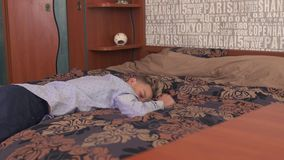 Το αγόρι πέφτει στο κρεβάτι και τους ύπνους απόθεμα βίντεο