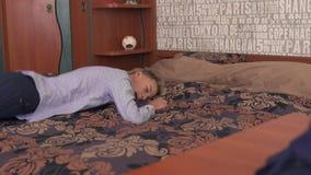 Το αγόρι πέφτει στο κρεβάτι και τους ύπνους φιλμ μικρού μήκους