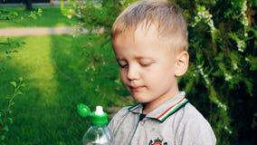 Το αγόρι πίνει πρόθυμα τους στεναγμούς νερού κατόπιν και χαμογελά φιλμ μικρού μήκους