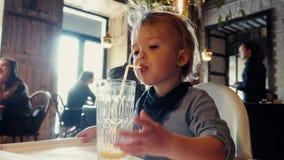 Το αγόρι πίνει τη συνεδρίαση γυαλιού χυμού από πορτοκάλι στον πίνακα στον καφέ φιλμ μικρού μήκους