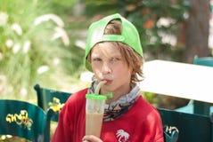 Το αγόρι πίνει τον πάγος-καφέ στο πάρκο Στοκ φωτογραφία με δικαίωμα ελεύθερης χρήσης