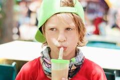 Το αγόρι πίνει τον πάγος-καφέ στο πάρκο Στοκ Εικόνες