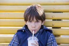 το αγόρι πίνει milkshake Στοκ Φωτογραφία