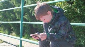 Το αγόρι παίζει ένα παιχνίδι στο κινητό τηλέφωνό του καθμένος στο πάρκο απόθεμα βίντεο