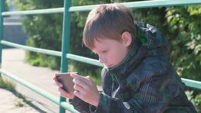 Το αγόρι παίζει ένα παιχνίδι στο κινητό τηλέφωνό του καθμένος στο πάρκο φιλμ μικρού μήκους