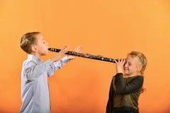 Το αγόρι παίζει το κλαρινέτο στο αυτί girl's, τα κύματα κοριτσιών τα όπλα της στοκ εικόνα με δικαίωμα ελεύθερης χρήσης