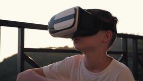 Το αγόρι παίζει στον υπολογιστή στα γυαλιά εικονικής πραγματικότητας στο ηλιοβασίλεμα στο ηλιοβασίλεμα Η έννοια σύγχρονου