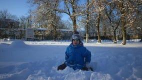 Το αγόρι παίζει στο χιόνι και γλείφει τα χείλια του από το χιόνι σε σε αργή κίνηση απόθεμα βίντεο