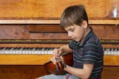 Το αγόρι παίζει την κιθάρα και παίρνει τις χορδές, dombra στο υπόβαθρο του πιάνου στοκ εικόνες με δικαίωμα ελεύθερης χρήσης