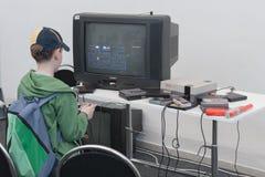 Το αγόρι παίζει την κονσόλα τυχερού παιχνιδιού με την τηλεόραση σε Animefest Στοκ Εικόνα