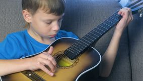 Το αγόρι παίζει τη συνεδρίαση κιθάρων στον καναπέ Έννοια της εκμάθησης να παίζεται ένα μουσικό όργανο απόθεμα βίντεο