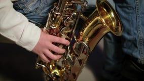 Το αγόρι παίζει το saxophone απόθεμα βίντεο