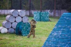 το αγόρι παίζει paintball στον τομέα δύο ομάδες των παικτών paintball στην κάλυψη διαμορφώνουν με τις μάσκες, κράνη, πυροβόλα όπλ στοκ εικόνες