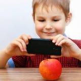 Το αγόρι παίρνει τις εικόνες της Apple σε Smartphone Στοκ εικόνα με δικαίωμα ελεύθερης χρήσης
