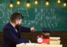 Το αγόρι, παιδί στη διαβαθμισμένη ΚΑΠ εξετάζει τις κακογραφίες στον πίνακα κιμωλίας ενώ ο δάσκαλος εξηγεί Ο δάσκαλος με τη γενειά Στοκ Φωτογραφία