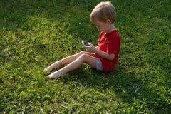 Το αγόρι παιδιών εξετάζει ένα κινητό τηλέφωνο καθμένος στη χλόη Η έννοια της εκπαίδευσης και της εξάρτησης στις συσκευές στα παιδ στοκ εικόνα