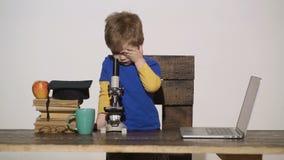 Το αγόρι παιδιών κοιτάζει στο μικροσκόπιο Έννοια Wunderkind - έξυπνο μικρό αγόρι, παιδί επιστημόνων που εργάζεται με το μικροσκόπ απόθεμα βίντεο