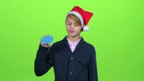 Το αγόρι παιδιών στην ΚΑΠ Άγιου Βασίλη αυξάνει το χέρι του και παρουσιάζει την κάρτα σε μια πράσινη οθόνη κίνηση αργή φιλμ μικρού μήκους