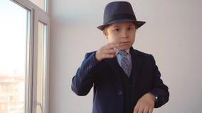 Το αγόρι παιδιών στο κοστούμι επιχειρηματιών εξετάζει τα ρολόγια και νευρικός στο γραφείο του απόθεμα βίντεο