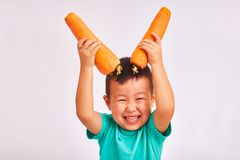 Το αγόρι παιδιών στο τυρκουάζ πουκάμισο, κρατά τα τεράστια καρότα απεικονίζοντας τα κέρατα - φρούτα και υγιή τρόφιμα στοκ φωτογραφίες