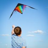 Το αγόρι πετά τον ικτίνο στο μπλε ουρανό στοκ εικόνα