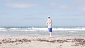 Το αγόρι πηγαίνει στη θάλασσα με έναν κάδο παιχνιδιών απόθεμα βίντεο