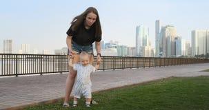Το αγόρι που κρατά το χέρι της μητέρας του κάνει τα πρώτα βήματα απόθεμα βίντεο