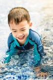 Το αγόρι που παίζει και που σέρνεται στην πισίνα στο χρόνο ηλιοβασιλέματος στο θερινή περίοδο στοκ εικόνες με δικαίωμα ελεύθερης χρήσης