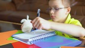 Το αγόρι που φορά eyeglasses και με το σπασμένο χέρι προσπαθεί να κάνει την εργασία με το αριστερό χέρι απόθεμα βίντεο