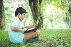 Το αγόρι προσέχει τον υπολογιστή στη χλόη στοκ φωτογραφία