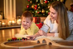 Το αγόρι προσέχει το mom του με το τραίνο παιχνιδιών στοκ φωτογραφία
