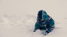 Το αγόρι ρίχνει το χιόνι και παίζει με το χιόνι φιλμ μικρού μήκους