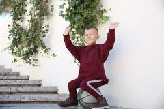 Το αγόρι σε ένα αθλητικό κοστούμι κάθεται σε μια σφαίρα στο πάρκο στοκ φωτογραφία με δικαίωμα ελεύθερης χρήσης