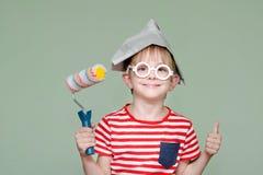 Το αγόρι σε ένα καπέλο και τα γυαλιά εγγράφου παρουσιάζει το δροσερό Πορτρέτο κύλινδρος Στοκ Εικόνα