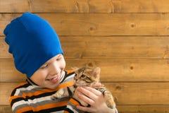 Το αγόρι σε ένα μπλε καπέλο κρατά ένα μικρό γατάκι, ενάντια σε έναν ξύλινο τοίχο Στοκ φωτογραφία με δικαίωμα ελεύθερης χρήσης