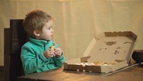Το αγόρι σε ένα πράσινο πουλόβερ τρώει μια πίτσα καθμένος σε μια ξύλινη καρέκλα πίτσα νόστιμη Το μικρό παιδί κρατά τη φέτα της πί απόθεμα βίντεο