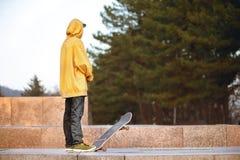 Το αγόρι στέκεται με skateboard στα φω'τα ηλιοβασιλέματος στοκ φωτογραφίες με δικαίωμα ελεύθερης χρήσης