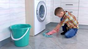 Το αγόρι στα λαστιχένια γάντια πλένει το πάτωμα στην κουζίνα Εγχώρια καθήκοντα παιδιού απόθεμα βίντεο
