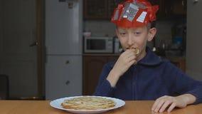 Το αγόρι στην έναρξη μασκών τρώει τις τηγανίτες και τον αντίχειρα επάνω απόθεμα βίντεο