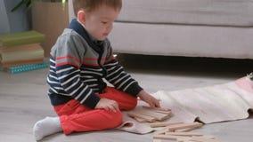 Το αγόρι στηρίζεται έναν πύργο από τους ξύλινους φραγμούς καθμένος στο πάτωμα από τον καναπέ απόθεμα βίντεο