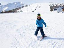 Το αγόρι στη μάσκα σκι μαθαίνει να κάνει σκι στο χιόνι προς τα κάτω Στοκ Φωτογραφία