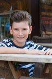 Το αγόρι στον πίνακα σε έναν καφέ οδών Η έννοια: μόδα hairstyle Στοκ φωτογραφία με δικαίωμα ελεύθερης χρήσης