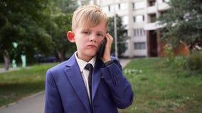 Το αγόρι στο επιχειρησιακό κοστούμι μιλά σε ένα κινητό τηλέφωνο στο πάρκο και Μπροστινή άποψη, πρόσωπο απόθεμα βίντεο