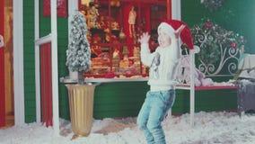 Το αγόρι στο καπέλο Santa που πηδά και που έχει τη διασκέδαση, που απολαμβάνει τα Χριστούγεννα απόθεμα βίντεο