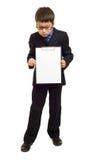 Το αγόρι στο κοστούμι παρουσιάζει κενό φύλλο Στοκ εικόνα με δικαίωμα ελεύθερης χρήσης