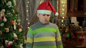 Το αγόρι στο πουλόβερ και το καπέλο Άγιου Βασίλη είναι και Δεν έχει κανένα δώρο Στα πλαίσια απόθεμα βίντεο