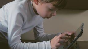 Το αγόρι στο τραίνο παίζει μια ταμπλέτα σε μια δεύτερης θέσης μεταφορά βάζοντας στο κατώτατο ράφι απόθεμα βίντεο