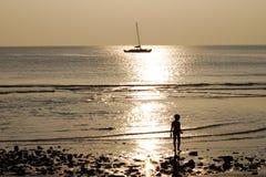 Το αγόρι συναντά ένα ηλιοβασίλεμα στην παραλία Στοκ Φωτογραφίες